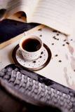 Alte Metallschreibmaschine, auf dem Tisch bedeckt im Staub und im rustCup des Kaffees Die Atmosphäre des Komforts und der Kreativ Lizenzfreie Stockbilder