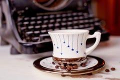 Alte Metallschreibmaschine, auf dem Tisch bedeckt im Staub und im rustCup des Kaffees Die Atmosphäre des Komforts und der Kreativ Stockfotos
