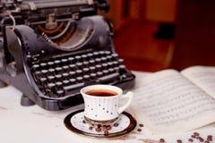 Alte Metallschreibmaschine, auf dem Tisch bedeckt im Staub und im rustCup des Kaffees Die Atmosphäre des Komforts und der Kreativ Stockfoto