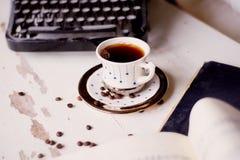 Alte Metallschreibmaschine, auf dem Tisch bedeckt im Staub und im rustCup des Kaffees Die Atmosphäre des Komforts und der Kreativ Stockfotografie