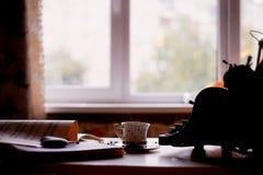 Alte Metallschreibmaschine, auf dem Tisch bedeckt im Staub und im rustCup des Kaffees Die Atmosphäre des Komforts und der Kreativ Lizenzfreies Stockfoto
