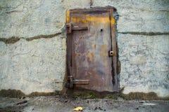 Alte Metalltür in einer Betonmauer stockbilder