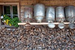 Alte Milchdosen an einer alpinen Hütte Stockfotografie