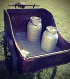 Alte Milchdosen transportiert durch einen alten Lastwagen mit rostigem Fahrrad Stockbilder