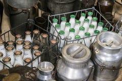 Alte Milchflaschen und Butterfässer Stockbilder