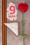 alte Militärbuchstaben mit Gartennelken, St- Georgeband und Aufschrift am 9. Mai auf einem Schrott des Blattes Stockfotografie