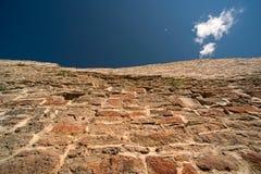 Alte mittelalterliche Backsteinmauer und Himmel Lizenzfreies Stockbild