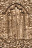 Alte mittelalterliche Holztür mit dekorativem Bogen und Autumn Leaves Lizenzfreies Stockfoto