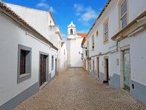 Alte mittelalterliche Straße in Lagos mit der Maria-Kirche in Portugal Lizenzfreie Stockfotografie