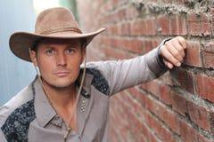 Alte mode del cowboy Ritratto del cappello da cowboy d'uso del giovane mentre stando contro il fondo del muro di mattoni Immagine Stock Libera da Diritti