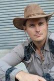 Alte mode del cowboy Ritratto del cappello da cowboy d'uso del giovane mentre stando contro il fondo metallico approssimativo del Immagine Stock
