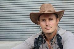 Alte mode del cowboy Ritratto del cappello da cowboy d'uso del giovane mentre stando contro il fondo metallico approssimativo del Fotografia Stock Libera da Diritti