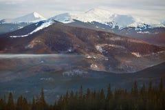 Alte montagne con i picchi nevosi al tramonto Fotografie Stock