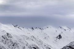 Alte montagne nevose e cielo grigio della tempesta prima della bufera di neve Immagini Stock Libere da Diritti