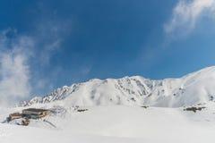 Alte montagne sotto neve con chiaro cielo blu Immagini Stock Libere da Diritti
