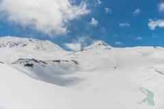 Alte montagne sotto neve con chiaro cielo blu Fotografia Stock Libera da Diritti