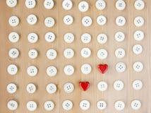 Alte nähende Knöpfe und zwei rote hölzerne Herzen in der Mitte als Muster Flache Lage, Draufsicht Lizenzfreie Stockfotos