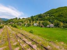 Alte nahe kleine ländliche Bahnhäuser vor dem hintergrund der hohen grünen Berge Lizenzfreies Stockbild