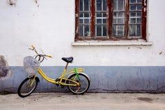 Alte Nebenstraße mit einem alten gelben Fahrrad der Weinlese Stockfoto