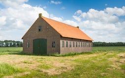 Alte niederländische Scheune der Ziegelsteinmaurerarbeit mit einem orange Ziegeldach Stockfotografie