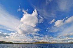 Alte nuvole sopra un lago a distanza Immagine Stock