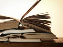 Alte offene Romanbücher auf einem Holztisch Stockbilder