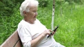 Alte Oma betrachtet Internet Smartphone stock footage