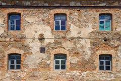 Alte orange Backsteinmauer mit sechs Fenstern Lizenzfreie Stockfotografie