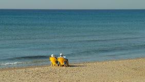 Alte Paare, die durch das Meer sich entspannen Lizenzfreie Stockfotos