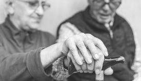 Alte Paare, die jede andere Hände halten stockbilder