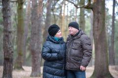 Alte Paare, die zusammen in den Wald hat eine gute Zeit gehen Lächeln und Unterhaltung auf Herbst oder Frühling Stockfoto