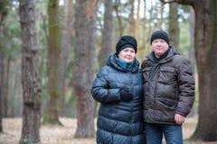 Alte Paare, die zusammen in den Wald hat eine gute Zeit gehen Lächeln und Unterhaltung auf Herbst oder Frühling Stockfotos