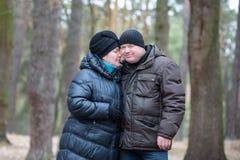 Alte Paare, die zusammen in den Wald hat eine gute Zeit gehen Lächeln und Unterhaltung auf Herbst oder Frühling Stockbild