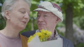 Alte Paare, Frau mit dem grauen Haar und Mann im Kappengeruch die gelben Blumen und die Unterhaltung Erwachsene Paare des zarten  stock video