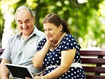 Alte Paare mit Tabletten-PC sitzen auf Bank. Stockbild