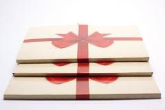 Alte Papierverpackung mit rotem Band und rotem Bogen Stockfotos