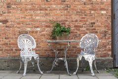 Alte, patinated Gartenmöbel gegen Backsteinmauer Stockfotos