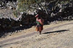 Alte peruanische Frau, die in die Berge geht Stockfotografie