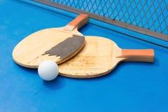 Alte Pingpongschläger und Ball und Netz auf blauer Pingpongtabelle Lizenzfreie Stockfotos