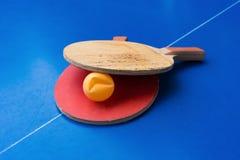 Alte Pingpongschläger und ein eingebeulter Ball auf blauer Pingpongtabelle stockfotografie