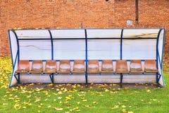 Alte Plastiksitze auf Stadionsspielern im Freien setzen auf die Bank Lizenzfreie Stockfotografie