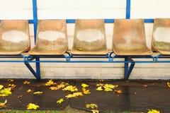Alte Plastiksitze auf Stadionsspielern im Freien setzen, Stühle mit abgenutzter Farbe unter gelbem Dach auf die Bank Ende von Fuß Lizenzfreie Stockfotografie