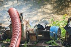 Alte Pumpe mit einem starken roten Feuerlöschschlauch ist trocknender Sumpf Pumpendes Wasser vom Teich Lizenzfreies Stockfoto