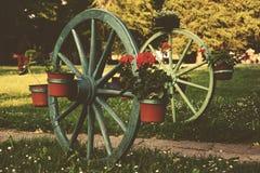 Alte Räder des Kampfwagens mit Blumendekoration Stockfotos