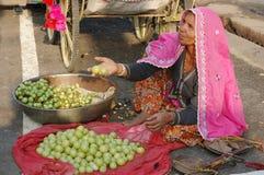 Alte rajasthani Frau, die Früchte am Markt während des angemessenen Feiertags des jährlichen Kamels in Pushkar verkauft Lizenzfreie Stockfotografie
