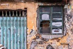 Alte raue graue Ziegelsteinwand mit gebrochenem Beton, abgezogener gelber Farbe und Formflecken Fenster mit schmutzigem Glas im H stockfotos