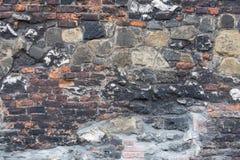 Alte raue Wand mit Ziegelsteinen und Steinen Stockfotografie
