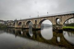Alte reflektierte Brücke im Fluss stockfoto