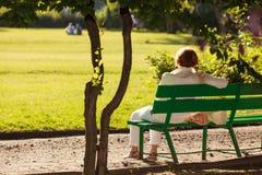 Alte reife Frau, die im Park sich entspannt Lizenzfreie Stockfotografie