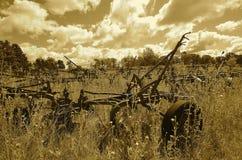 Alte Reisepflüge in einem Feld Sepia Stockfoto